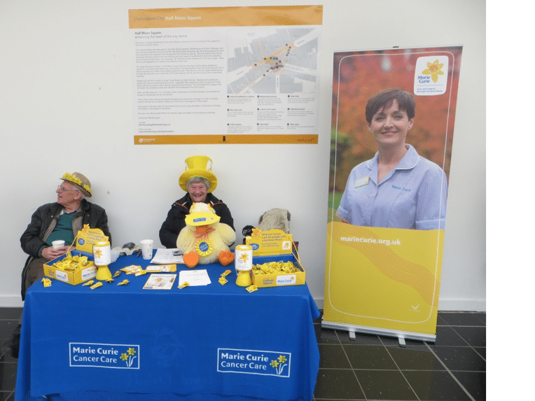 Marie Curie Cancer Care two people sat at a charity table